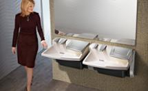 Woman admiring at the all-in-one Advocate AV-Series lavatory system with soap water and hand drier in the same fixture