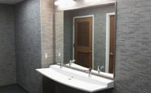 Grey restroom with a Verge L-Series Lavatory deck in white Anatarctica Evero Solid Quartz Material